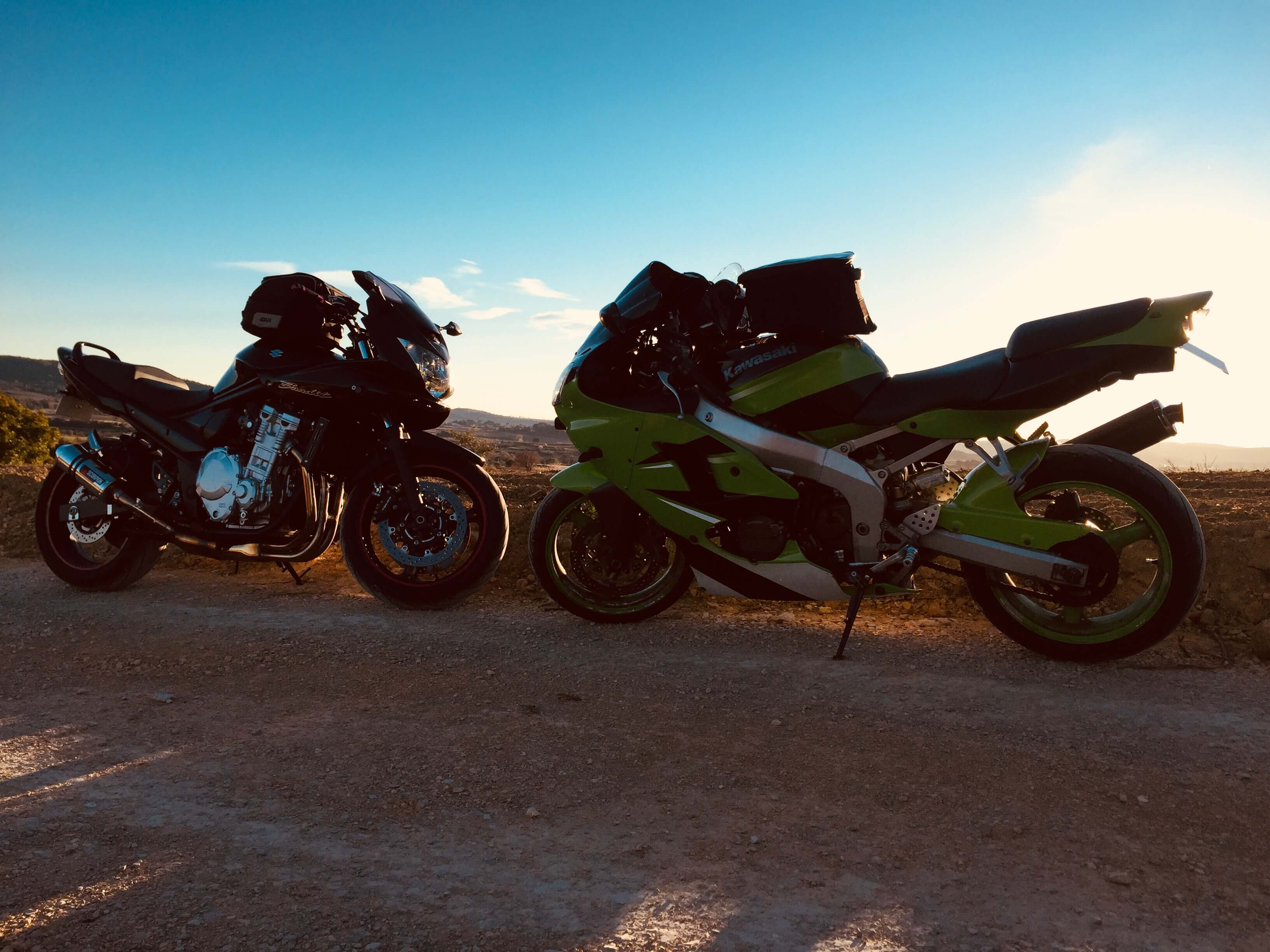 2 motos équipées de sacs de réservoir stationnées devant le coucher de soleil
