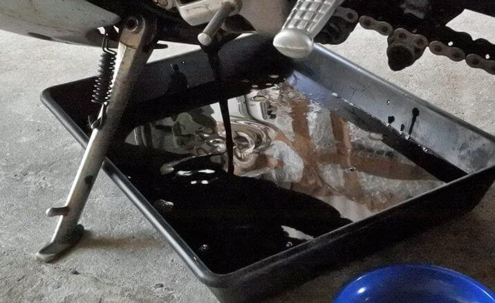 Récipient de récolte de l'huile usagée placée sous une moto