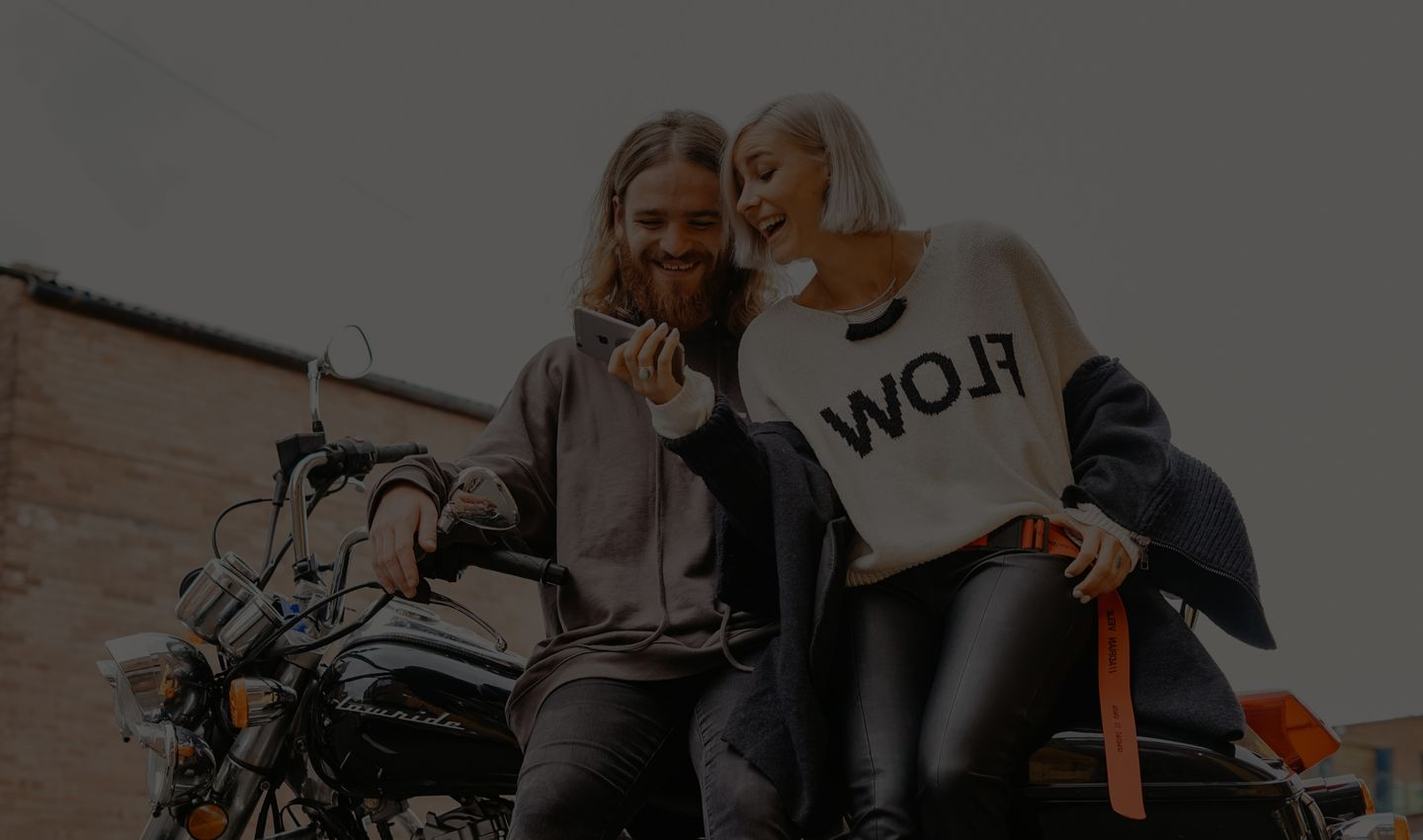 Photo d'un couple souriant sur une moto en regardant un smartphone